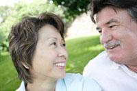 芝生の上に座る50代男性と女性