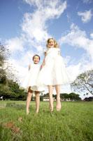 公園でジャンプするドレス姿の女の子2人