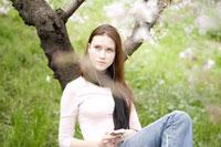 桜の木の下で音楽を聴く女性