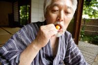 お団子を食べているシニア男性