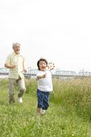 風車で遊ぶおじいちゃんと孫