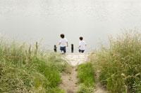河川敷で遊ぶ兄弟の後ろ姿