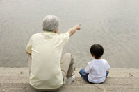 河川敷に座るおじいちゃんと孫 02299004181| 写真素材・ストックフォト・画像・イラスト素材|アマナイメージズ