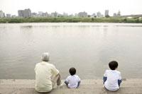 河川敷に座るおじいちゃんと孫 02299004182| 写真素材・ストックフォト・画像・イラスト素材|アマナイメージズ