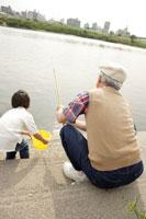 河川敷で釣りをする祖父と孫