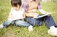 屋外で絵を描くおじいちゃんと孫