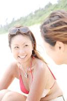 砂浜に座っている20代女性2人