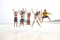 浜辺でジャンプする若者7人