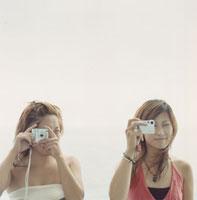 デジカメを構える20代女性2人 02299004290| 写真素材・ストックフォト・画像・イラスト素材|アマナイメージズ