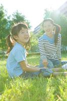 芝生の上に座る日本人の母と娘