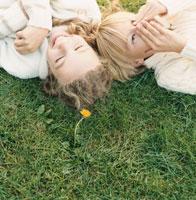 芝生の上で寝転ぶ外国の男の子と女の子