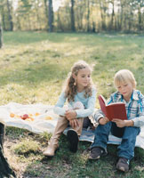 屋外で読書をする外国の男の子と女の子