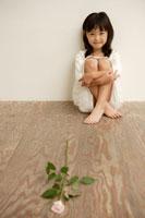 床の上に座る女の子とバラの花