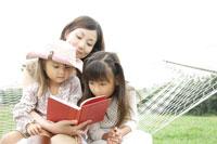 ハンモックに座って本を読む母と娘