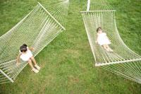 ハンモックの上に寝ている女の子2人 02299004646| 写真素材・ストックフォト・画像・イラスト素材|アマナイメージズ