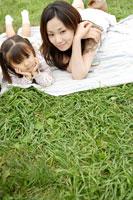 芝生の上に寝転ぶ親子