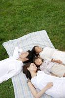 芝生の上に寝転ぶ家族