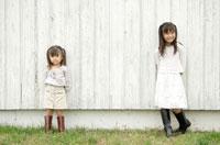 壁際に立つ女の子2人