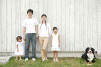 壁際に立つ家族と犬