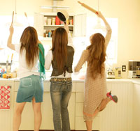 キッチンで料理を作る女性3人の後姿