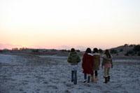 砂浜を歩く女性4人