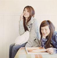 雑誌を読む女性と携帯で話す女性