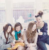 携帯を持っている女性4人