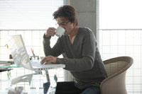 マグカップを片手にパソコン作業の男性