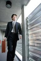 廊下を歩く眼鏡をかけた男性 02299004966| 写真素材・ストックフォト・画像・イラスト素材|アマナイメージズ