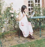 庭で本を読む20代女性