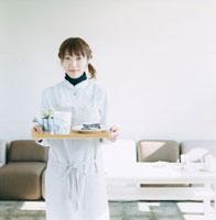 ケーキをのせたトレイを持っている女性