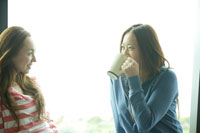 窓辺で話す20代女性2人