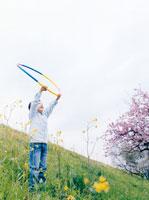 フラフープを持って野原に立つ男の子 02299005340| 写真素材・ストックフォト・画像・イラスト素材|アマナイメージズ