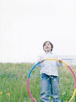 フラフープを持って野原に立つ男の子