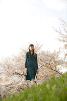 土手を歩く女性と桜
