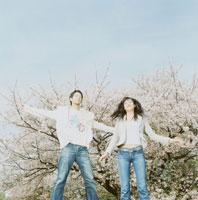 桜の前でジャンプする男女