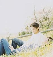 土手に寝そべるカップル 02299005494| 写真素材・ストックフォト・画像・イラスト素材|アマナイメージズ