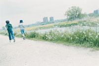 河沿いの道を走る少年の後姿