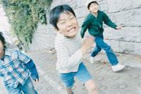 坂道を走る3人の少年
