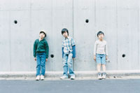 壁にもたれて立つ少年3人