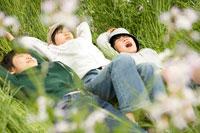 草の上に寝転がる少年3人