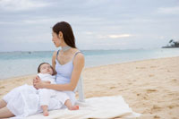 砂浜に座るお母さんと赤ちゃん