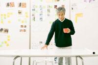 机の前でコーヒーを飲むビジネスマン