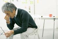 椅子に座り考えるビジネスマン