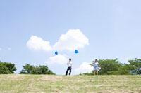 風船を持ち芝生に立つ女子学生と男子学生 02299005929| 写真素材・ストックフォト・画像・イラスト素材|アマナイメージズ