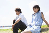 土手に座り微笑む女子学生と男子学生 02299005932| 写真素材・ストックフォト・画像・イラスト素材|アマナイメージズ