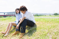 土手に座り微笑む女子学生と男子学生 02299005933| 写真素材・ストックフォト・画像・イラスト素材|アマナイメージズ