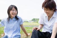 土手に座り微笑む女子学生と男子学生 02299005934| 写真素材・ストックフォト・画像・イラスト素材|アマナイメージズ