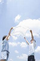 布を広げる女子学生と男子学生 02299005952| 写真素材・ストックフォト・画像・イラスト素材|アマナイメージズ