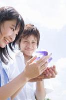 小鳥を手に取る女子学生と男子学生 02299005957| 写真素材・ストックフォト・画像・イラスト素材|アマナイメージズ